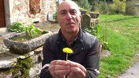 An elderly man kneels with a dandelion flower