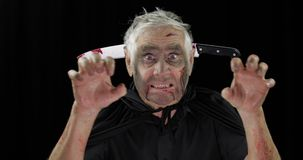 Elderly man with knife in head. Halloween makeup and costume. Blood on his face