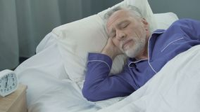 Elderly man lacks in strength and energy to wake up from bed early in morning. Stock footage stock video footage