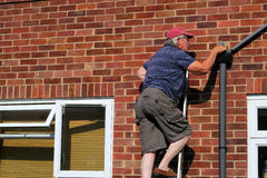 Elderly man on a ladder. An elderly man climbing on a ladder doing repairs to his house Stock Images