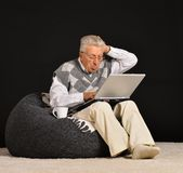 Elderly man with laptop Stock Photography