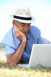 Elderly man laying in field. With laptop Royalty Free Stock Image