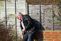 Elderly or old man feeling ill. An elderly or old  man leaning against a wall holding a walking stick and feeling ill. In pain and bent over Stock Images