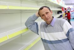 Elderly man leans against empty shelves Royalty Free Stock Image