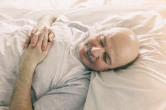 An elderly man lies on a bed and closes his eyes Royalty Free Stock Photography