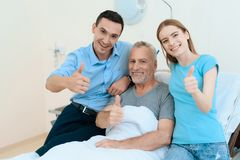 An elderly man lies in a hospital room on a bed. He is seen by a man with a woman. stock photos