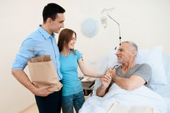 An elderly man lies in a hospital room on a bed. He is seen by a man with a woman. They are standing next to his bunk. An elderly men lies in a hospital room on Stock Image
