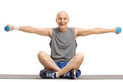 Elderly man lifting dumbbells and sitting on an exercise mat. Isolated on white background Royalty Free Stock Photo