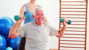 Elderly man lifting hand weights sitting on exercise ball with his trainer. At the rehabilitation center stock footage
