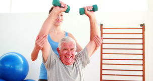 Elderly man lifting hand weights sitting on exercise ball with his trainer. At the rehabilitation center stock video