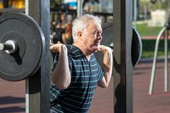Elderly man lifting weights in Outdoors Gym Royalty Free Stock Image