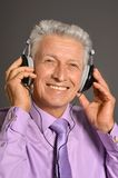 Elderly man listen to music in headphones Stock Image