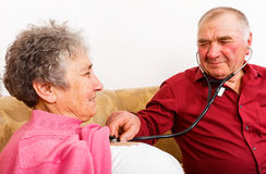 Elderly man listening his wife heartbeat royalty free stock image