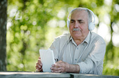 Elderly man listening to music on a tablet Royalty Free Stock Photo