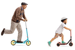 Elderly man and a little boy riding scooters Stock Photos