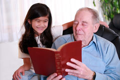 Elderly man and little girl reading Bible together Royalty Free Stock Photography