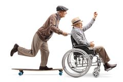 Elderly man on a longboard pushing a man with raised hand in a wheelchair. Full length profile shot of an elderly men on a longboard pushing a men with raised stock photography