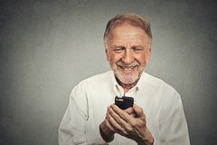 Elderly man looking at his smart phone while text messaging Stock Images
