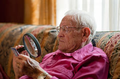 Elderly man looking at object with magnifier royalty free stock images