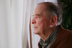 Elderly man looking out window. Elderly man looking sadly out window Royalty Free Stock Images