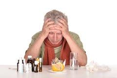 Elderly  man  looking at pills Royalty Free Stock Image