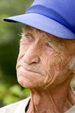 An elderly man looks into the distance. Senior pensive man in cap looks into the distance Stock Photography