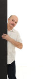 Elderly man looks out from behind black wall Royalty Free Stock Photography