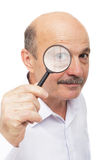 Elderly man looks at something through a magnifying glass. Royalty Free Stock Photos