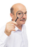 Elderly man looks at something through a magnifying glass. Royalty Free Stock Photo