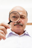 Elderly man looks at something through a magnifying glass. Royalty Free Stock Photography