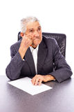 Elderly man lost in deep thought holding a pen and a sheet of p Stock Photo