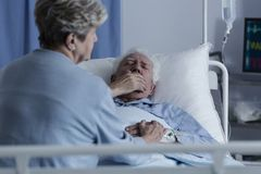 Elderly man with lung cancer. Elderly men with lung cancer lying in a hospital bed and coughing stock photo