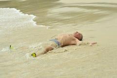Elderly man lying  on beach Royalty Free Stock Images