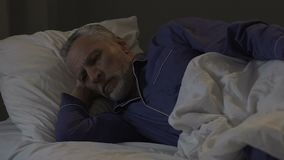 Elderly man lying in bed at night unable to sleep, insomnia, disturbing thoughts. Stock footage stock video footage