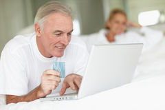 Elderly man lying on bed and shopping online Stock Photo