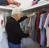 Elderly Man Making Arranging Clothing In Wardrobe. Royalty Free Stock Photos