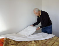 Elderly Man Making His Bed. Royalty Free Stock Image
