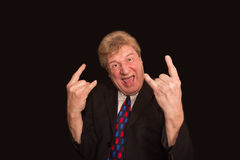 Elderly man making a horns gesture depicting heavy metal rock music. On a dark background with copyspace Royalty Free Stock Image