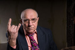 Elderly man making a horns gesture Royalty Free Stock Photo