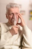 Elderly man making inhalation Stock Image