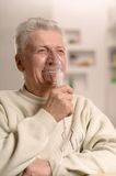 Elderly man making inhalation Royalty Free Stock Photos