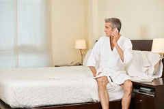Elderly man making phone call in hotel room Royalty Free Stock Photos