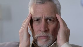 Elderly man massaging temples, suffering from migraine disorder, health problems. Stock footage stock footage