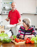 Elderly man and mature woman  doing chores Stock Photos