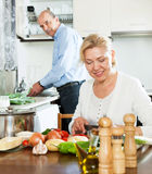 Elderly man and mature woman doing housework Royalty Free Stock Photo