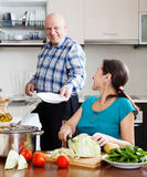 Elderly man and mature woman  doing housework together Royalty Free Stock Photography