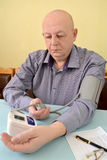 The elderly man measures pressure by an electronic tonometer sem. Iautomatic device stock image
