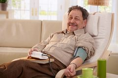 Elderly man measuring blood pressure Royalty Free Stock Photos
