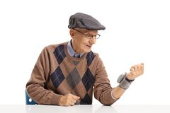 Elderly man measuring blood pressure with a wrist device royalty free stock photos
