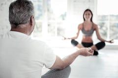 Elderly man meditating during yoga session Stock Photography